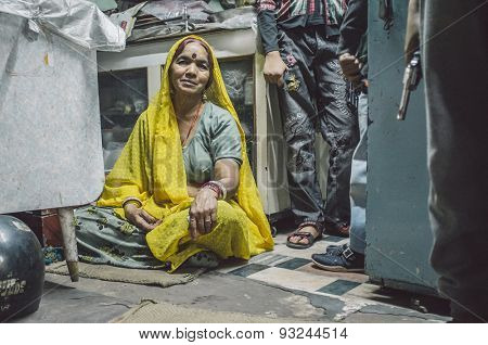 JODHPUR, INDIA - 16 FEBRUARY 2015: Woman sitting on floor of store while children stand next to her holding toy guns. Post-processed with grain and texture.