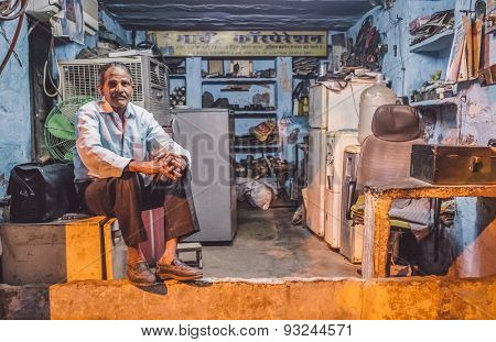 JODHPUR, INDIA - 10 FEBRUARY 2015: Elderly electrician sits on fridge before closing refrigerator service shop. Post-processed with grain and texture.