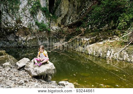 Tired And Annoyed Little Girl Resting On A Big Rock
