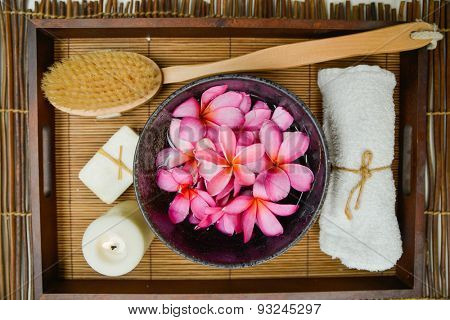 bowl in many frangipani in basket with towel, candle,soap on mat