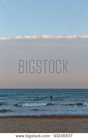Golden Sunset Light Of A Silhouette Of A Surfer On His Board Moving Towards The Sea At The Beach Wit
