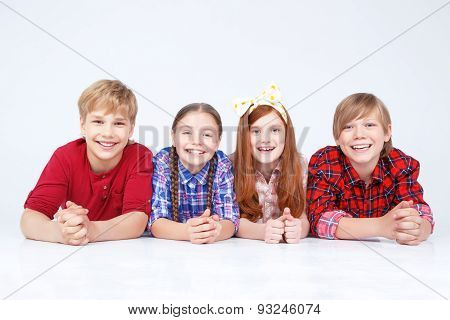Smiling children lying on the floor in raw