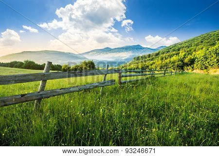 Fence On Hillside Meadow In Mountains At Sunrise