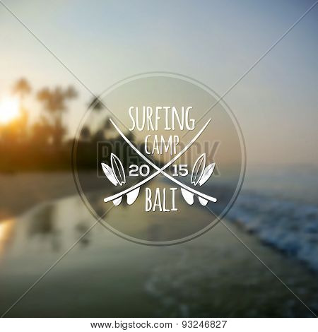 White surfing camp logo on blurred ocean sunrise photo background