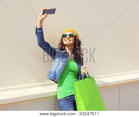 Fashion Happy Pretty Cool Young Woman With Shopping Bags Makes Photo Self-portrait On The Smartphone