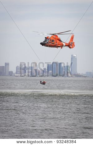 STATEN ISLAND, NY - MAY 24 2015: A Coast Guard rescue swimmer sitting in a rescue basket is hoisted into a USCG MH-65 Dolphin helicopter for a Search and Rescue demonstration during Fleet Week 2015.