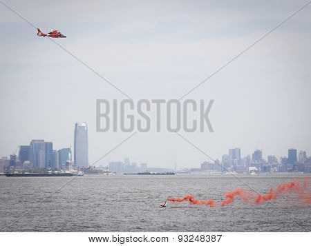 STATEN ISLAND, NY - MAY 24 2015: Orange smoke from a flare held by a rescue swimmer signals a US Coast Guard MH-65 Dolphin helicopter during a Search and Rescue demonstration for Fleet Week 2015.