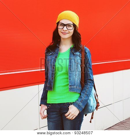 Portrait Of Pretty Girl In Glasses Wearing A Bright Casual Clothes Against The Colorful Red Wall