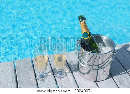 Cold champagne bottle in ice bucket and two glasses of champagne on the deck by the swimming pool