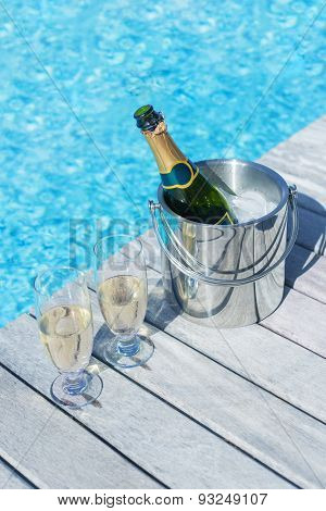 Vertical photo of champagne bottle in bucket and two glasses of champagne on the deck by the swimmin
