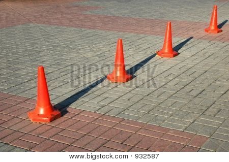 Red Road Cones Aligned In Row With Shadows