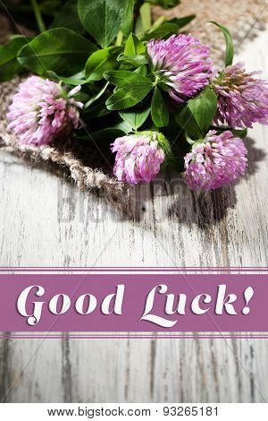 Clover flowers on wooden surface with text Good Luck
