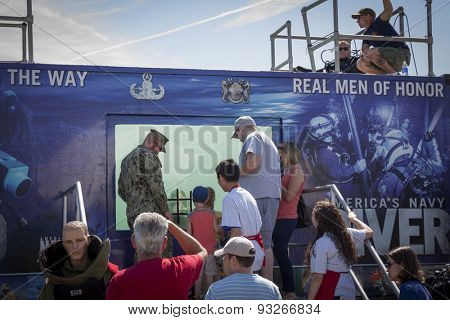 STATEN ISLAND, NY - MAY 24 2015: Children line up to play tic tac toe against a U.S. Navy EOD technician through the glass of a 6,800 gallon mobile dive tank on Sullivans Pier at Fleet Week NY 2015.
