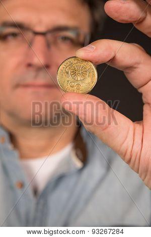 Man Holding Greek Drachma Coin