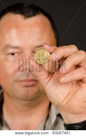 Man Holding Greek Drachma Coin