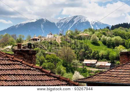 Bulgarian Mountain Village, Small Chapel And Snow Mountain in The Distance.