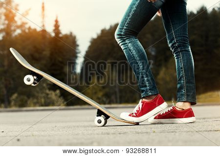 Lady with red shoes standing on the asphalt road with skate board