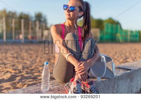Beautiful fitness athlete woman wearing sunglasses listening music resting after work out exercising