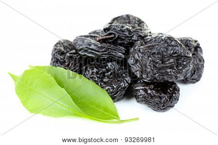 Pile of prunes with green leaves isolated on white