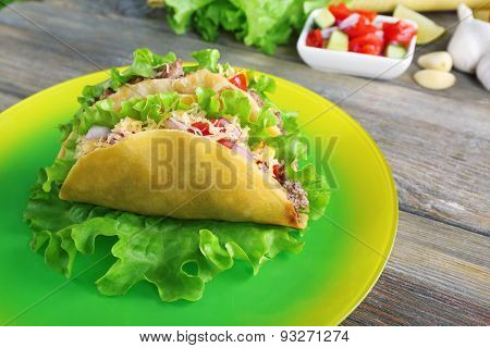 Tasty taco on plate with vegetables on table close up