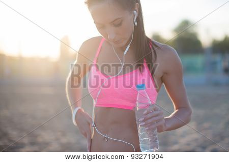 Beautiful fitness athlete woman resting drinking water after work out exercising on beach summer eve