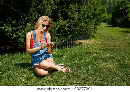 Happy Young Blonde Woman College Student Use Tablet Pc Sit On Grass In Park.