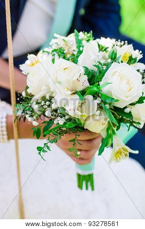 Bridal bouquet and hands of  bride and groom
