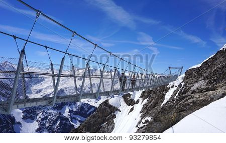 Suspended Walkway Over Snow Mountains