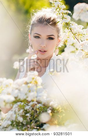 Beautiful happy woman in a flowery spring garden.