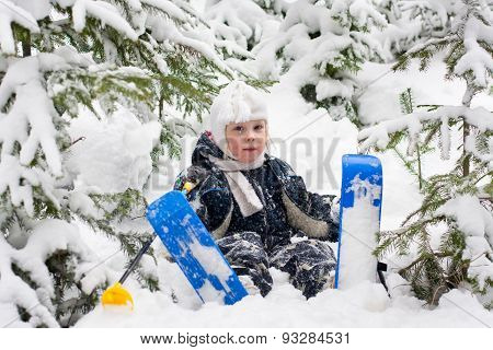 Little Girl In Skiing Sits On The Snow