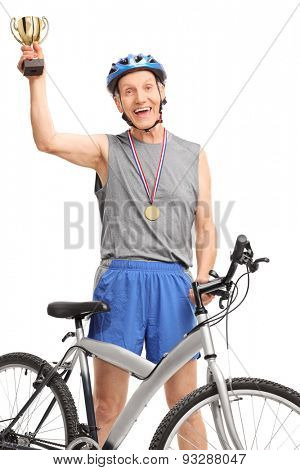 Vertical shot of an overjoyed senior cyclist holding a golden trophy and looking at the camera isolated on white background
