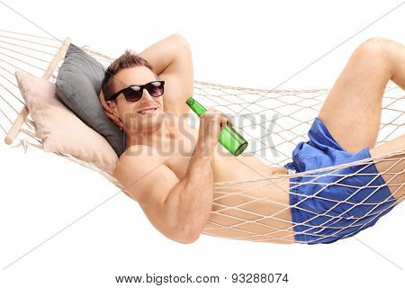 Relaxed young man lying in a hammock and drinking a beer isolated on white background