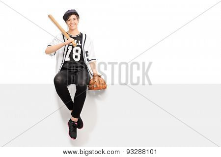 Young woman holding a baseball bat and wearing a baseball glove seated on a panel isolated on white background
