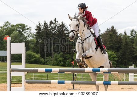 Horsewoman In Red Jacket Is Jumping On A White Horse