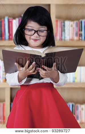 Attractive Child With Book In Library