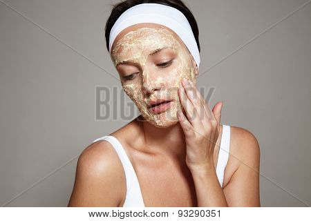 Woman Touching Her Face With A Facial Mask