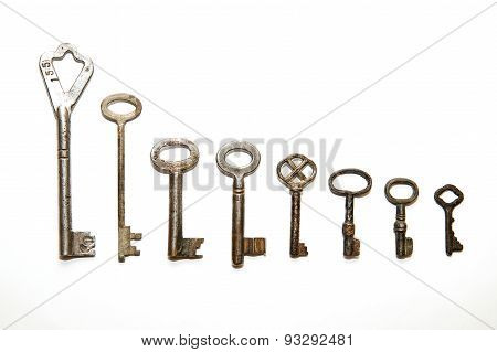 Many Old Keys To The Safe On A White Background