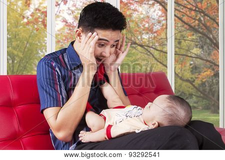 Father Play Peekaboo With His Baby