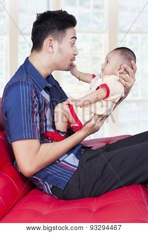Joyful Father Play With His Kid On Sofa