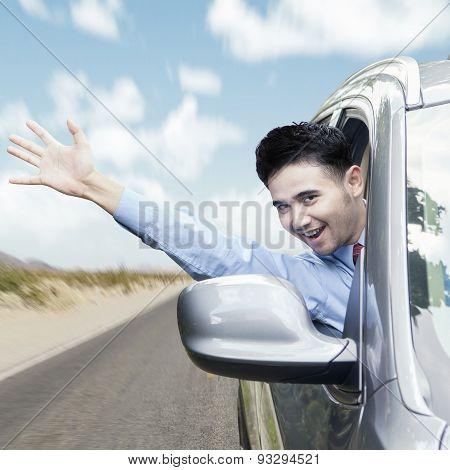 Joyful Man Waving Hand In The Car