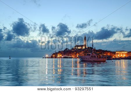 Mediterranean town of Rovinj in Istra, Croatia at dusk on the Adriatic sea with a boat