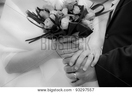 Bride and groom holding hands and bridal bouquet with their wedding rings