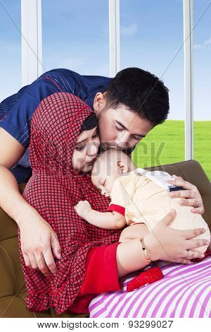 Young Muslim Parents Kiss Their Kid