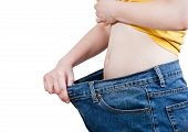 foto of emaciated  - grown thin girl trying on large size old jeans isolated on white background - JPG