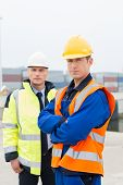 pic of coworkers  - Portrait of confident worker standing with coworker in shipping yard - JPG