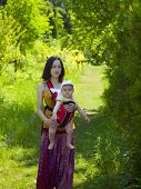 pic of sling bag  - Young mother walking in the Park and holding a small child in a Baby Carrier bag.
