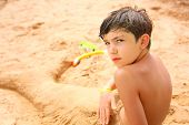 stock photo of preteen  - preteen handsome boy in the sand sculpture of mermaid tail with tube and snorkeling mask - JPG