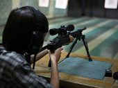 stock photo of shooting-range  - a child shooting a sniper rifle at a gun range - JPG