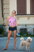 picture of poodle  - Beautiful young woman on a walk with cute poodle dog - JPG