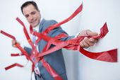 stock photo of trap  - Businessman trapped by red tape on white background - JPG